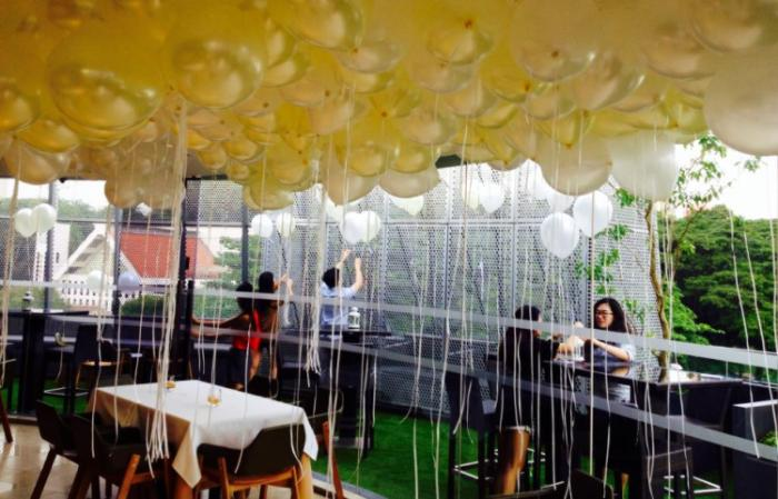 Indoor seating area with golden balloons at the ceiling